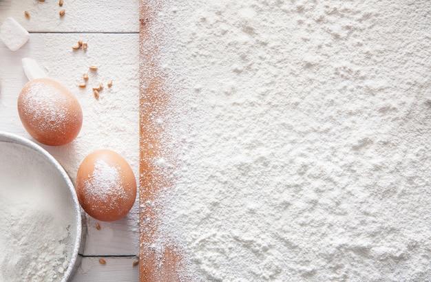 Backklasse oder rezeptkonzepthintergrund, eier und bestreutes weizenmehl auf holzbrett auf tisch. teig oder gebäck kochen.