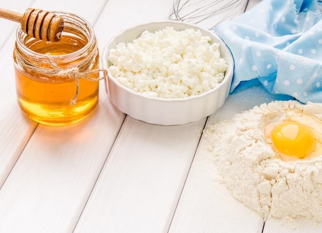Backkuchen in der rustikalen küche - teigrezept zutaten eier, mehl, milch, butter, honig auf weißem holzbrett tisch von oben