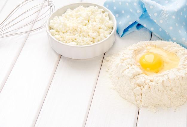 Backkuchen in rustikaler küche - teigrezept zutaten eier, mehl, milch, butter, zucker auf weißem holzbrett tisch von oben