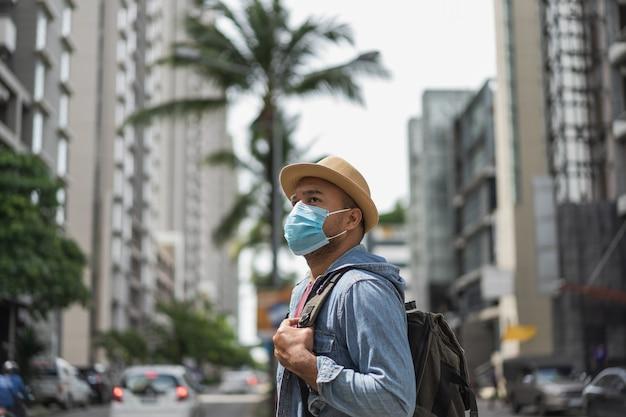 Backpacker, der in der stadt reist, die gesichtsmaske trägt.