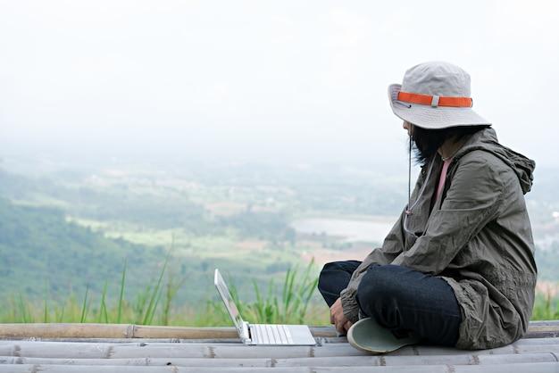 Backpacker entspannen sich in der natur und nutzen den laptop für die kommunikation