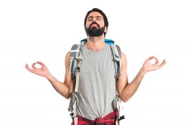 Backpacker in zen-position auf weißem hintergrund