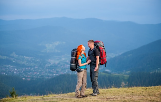 Backpacker-kerl und rothaarige mädchenstellung