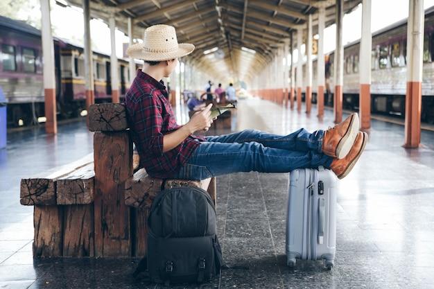 Backpacker sitzen da, um die reisedetails mit seiner karte zu überprüfen, während sie darauf warten, dass der zug am bahnhof ankommt