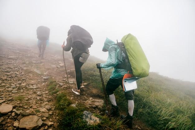 Backpacker wandern die nebligen berge hinauf. bergwandern. männer mit rucksäcken unterwegs