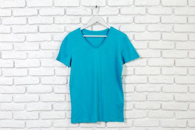 Backstein weiß getünchte wand mit t-shirt auf kleiderbügel