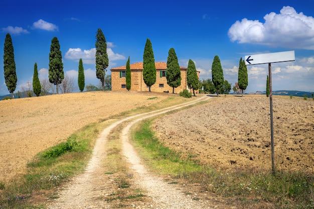 Backsteinhaus in der landschaft von toskana, italien. der weg zum haus. ländliche landschaft.