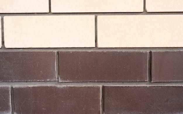 Backsteinmauer hintergrund, gelbe und braune farben, backsteinmauer aus naturziegel zweifarbige steine. ziegelsteinbeschaffenheit für hintergrund oder entwurf