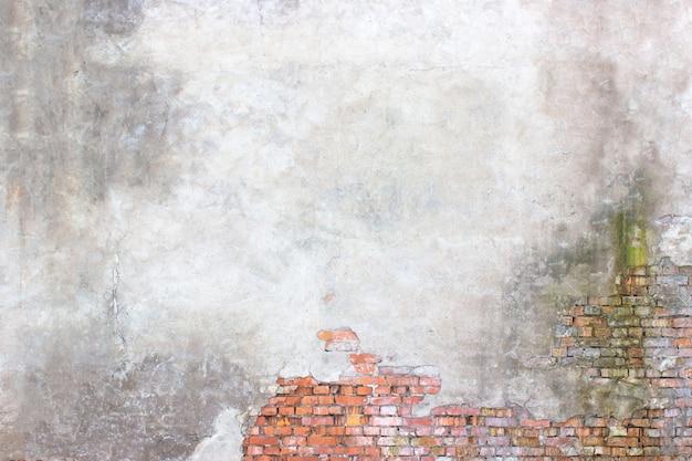 Backsteinmauer mit beschädigtem putz, hintergrund zerbrochene zementoberfläche
