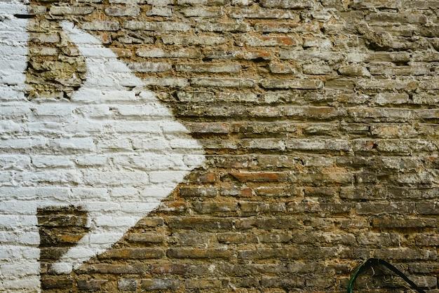 Backsteinmauer mit dem großen weißen pfeil, der richtung, hintergrund mit kopienraum anzeigt.