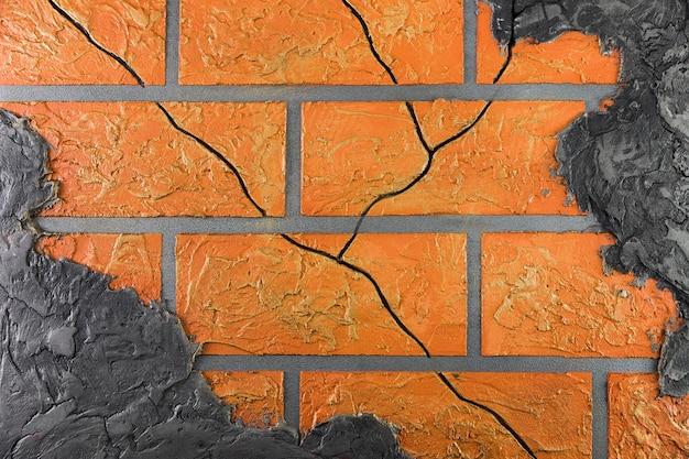 Backsteinmauer mit den sprüngen, die durch wand spähen