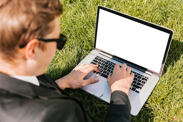 Backview-geschäftsmann, der laptop auf grünem gras verwendet