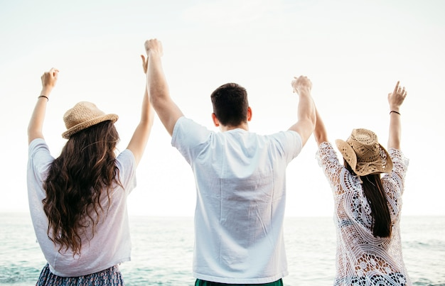 Backview von freunden am strand, der ihre arme anhebt