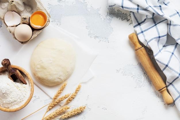 Backwand mit teig und zutaten für die zubereitung von nudeln oder pfannkuchen, eiern, mehl, wasser und salz auf weißem rustikalem alten tisch. draufsicht.