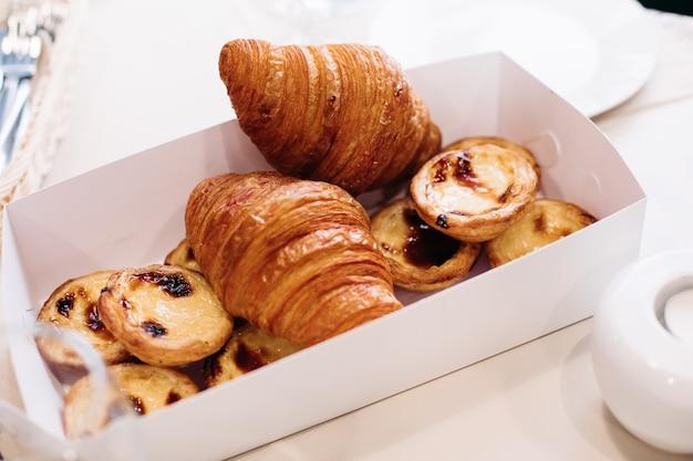 Backwaren, gebackene süße croissants, kuchen in verpackungskarton auf dem tisch zum frühstück. hotelverpflegung. foto in hoher qualität