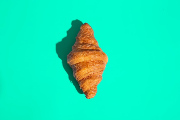 Backwaren gebackenes croissant. grüner hintergrund, ansicht von oben. pop-art-stil. leckeres und essenskonzept.