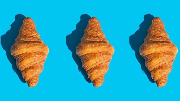 Backwarenmuster mit gebackenem croissant. blauer hintergrund, ansicht von oben. pop-art-stil. leckeres und essenskonzept.