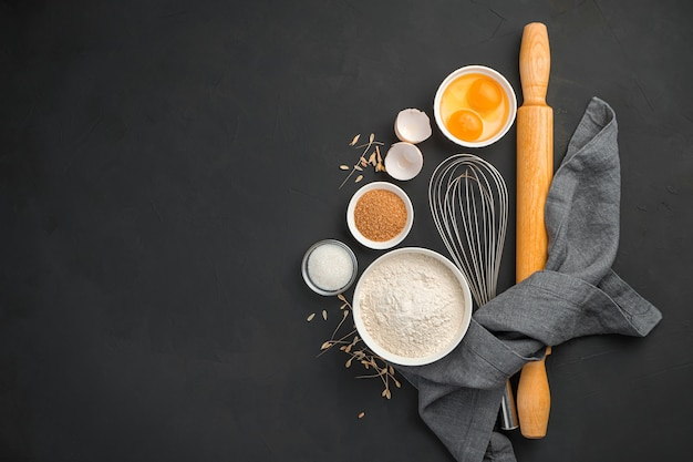 Backzutaten auf schwarzem hintergrund mehl, eier und zucker, die teiggerichte kochen, hintergrund kochen