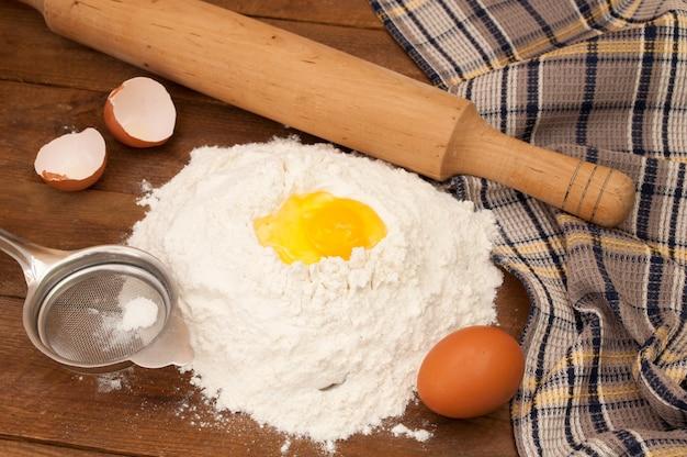 Backzutaten: eier und mehl, sieb und nudelholz auf holzhintergrund.
