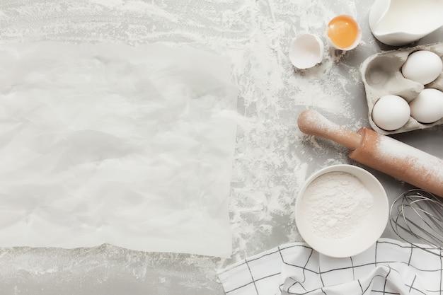 Backzutaten, küchenutensilien, weihnachtsplätzchen kochen auf grauem betonhintergrund flach, kopienraum. teig, eigelb, schüsselmehl, nudelholz, milch, pergamentpapier, nudelholz vorbereiten