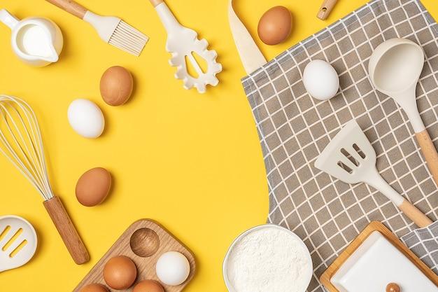 Backzutaten und kochutensilien mit kopienraum auf gelbem hintergrund. vorlage für kochrezepte oder ihr design. ansicht von oben flach legen.