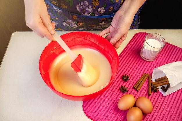 Backzutaten und utensilien zum kochen von biskuit. prozess kochen biskuit. frau, die den teig mischt