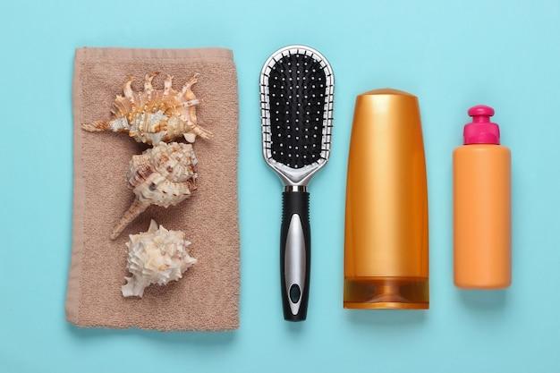 Bad schönheitsprodukte. flasche shampoo, herzmuscheln, handtuch, haarbürste auf blau