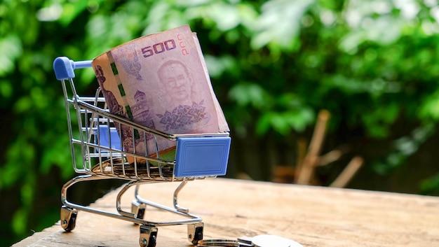 Badbanknote des geldes 500 auf rollenmünze mit warenkorb bei tisch im hellen licht des natürlichen baums der unschärfe. konzept finanziell, kauf von barzahlung für waren und dienstleistungen.