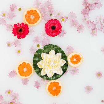 Bade-milch mit blumen und grapefruitscheiben dekoriert