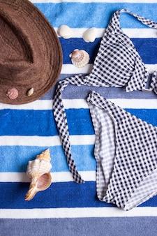 Badeanzug mit strandzubehör auf blauem hintergrund