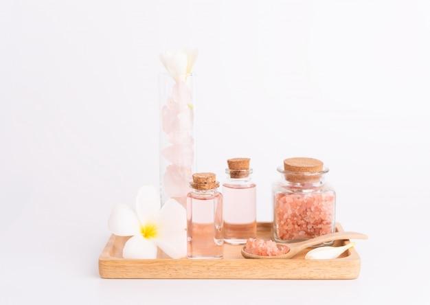 Badekur mit rosafarbener flüssigseife, rosa salz, steinen und plumeriablume auf hölzernem behälter über weiß