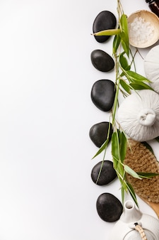 Badekurort-hintergrund mit massagekompressenbällen, steinen, seesalz, bürste und teekanne