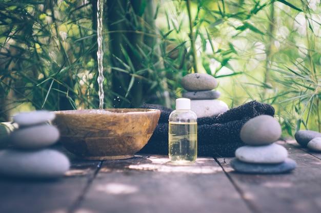 Badekurort mit den frauenhänden und klarem wasser auf einem alten holz