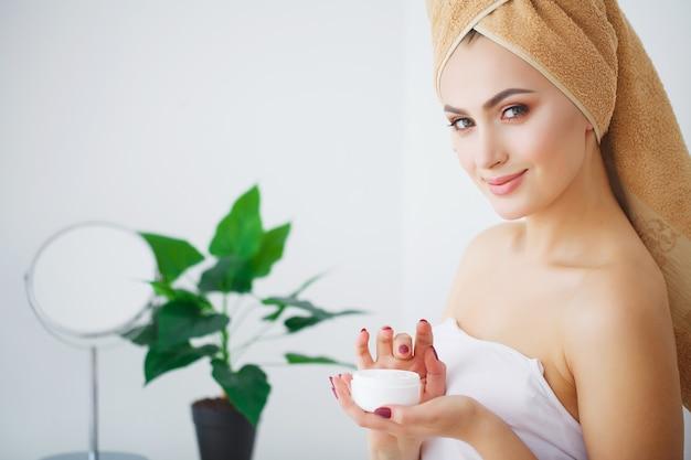 Badekurort, schönes modell, das kosmetische sahnebehandlung auf ihrem gesicht aufträgt