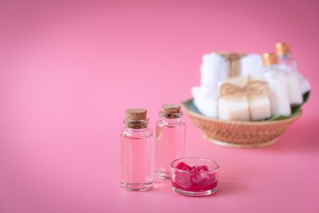 Badekurort wellnesskonzept mit roter kerze, flüssiger flasche der rose, milchseife, weiße tücher im hölzernen behälter