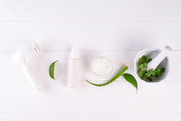 Badekurorthintergrund mit handgemachten naturkosmetikprodukten der vorbereitung und gesichtsbürste auf weißem holz