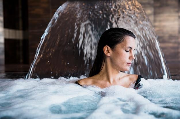 Badekurortkonzept mit der frau, die im wasser sich entspannt