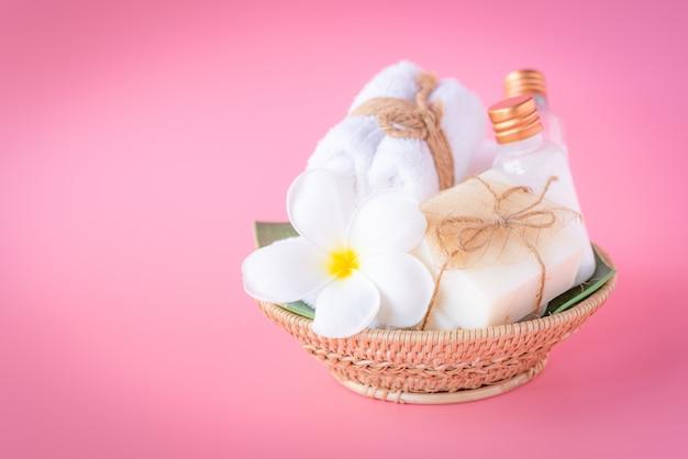Badekurortkonzept, rosafarbene flüssige flasche, milchseife, weiße tücher im hölzernen behälter auf rosa