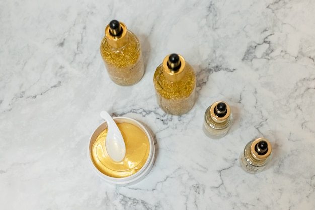 Badekurortkosmetik auf weißem marmorhintergrund von oben. beauty-blogger. hautpflegeprodukte. öl, creme, hydrogel goldene kosmetische augenklappe glas.