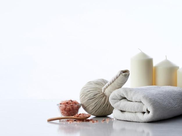Badekurortmassagekonzept, kräuterkompressenball, creme, blumenseife, duftende kerze und rosa himalajasalz, lokalisiert