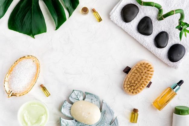 Badekurortschönheitskosmetik der flasche, palmblatt, organische seife, bürste auf weißer tabelle