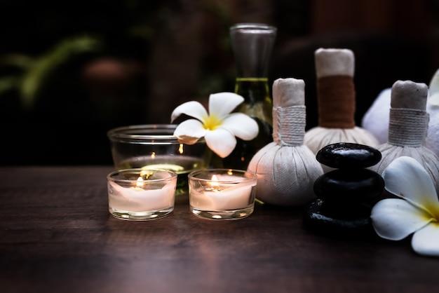 Badekurortstillleben mit weißer orchidee, seesalz, badeöl und kerze auf bretterboden, entspannender betrug
