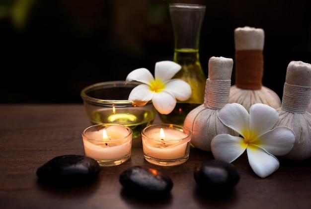 Badekurortstillleben mit weißer orchidee, seesalz, badeöl und kerze auf bretterboden.
