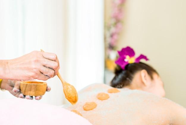 Badekurorttherapeut setzt peeling auf eine frauenrückseite auf