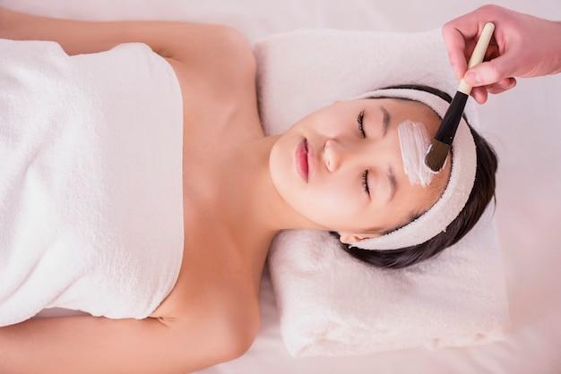 Badekurorttherapie für die junge asiatische frau, die gesichtsmaske empfängt.