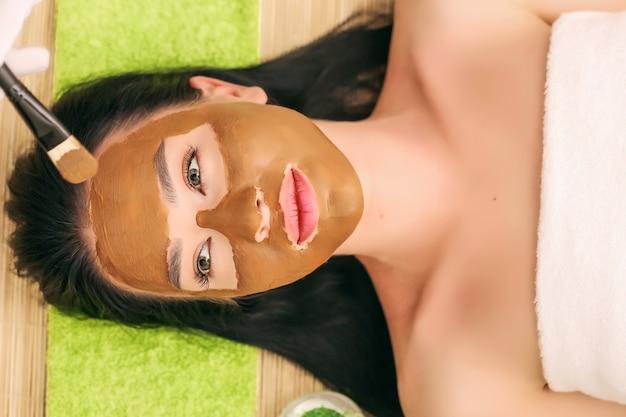 Badekurorttherapie für die junge frau, die kosmetische maske am schönheitssalon hat