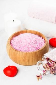 Badesalz mit aroma einer rose in einer hölzernen schüssel, in den blumenblättern und in einer frischen rosarose, in den tüchern und in den kerzen auf einem weißen hintergrund