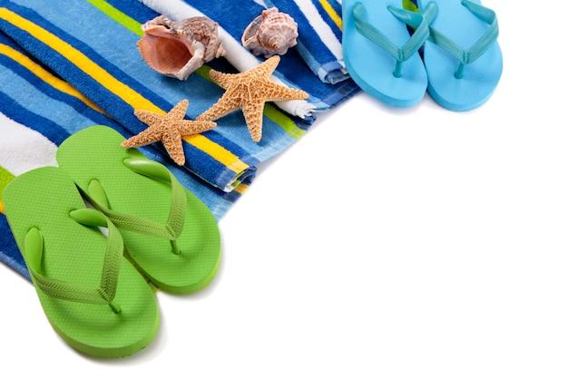 Badetuch mit den flipflops, starfish und muscheln lokalisiert auf weiß.
