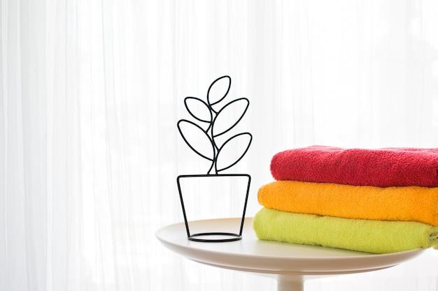 Badetücher in verschiedenen farben in der nähe einer dekorativen blume auf hellgrauem hintergrund.
