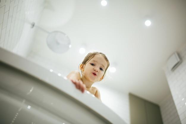 Badezeit macht spaß. bild des selektiven fokus eines netten kleinen mädchens, das ein bad und ein spiel nimmt